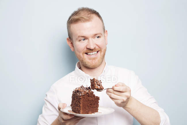Man eating chocolate cake — Stock Photo