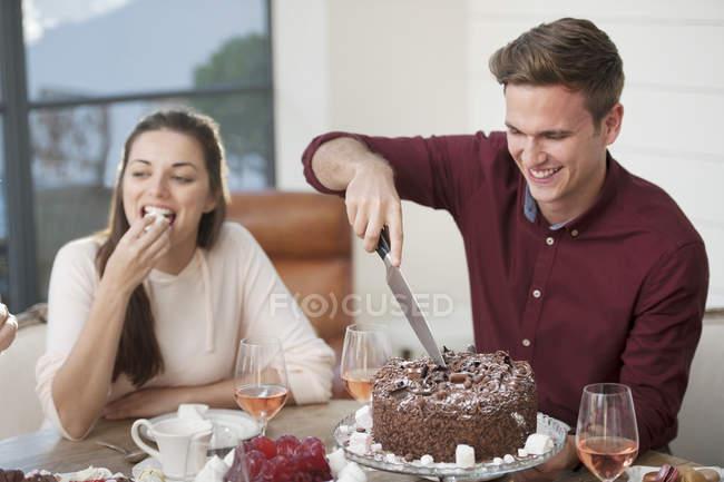 Man cutting chocolate birthday cake Stock Photo 158207386