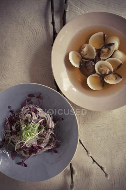 Bol de soupe de palourdes et assiette de salade — Photo de stock