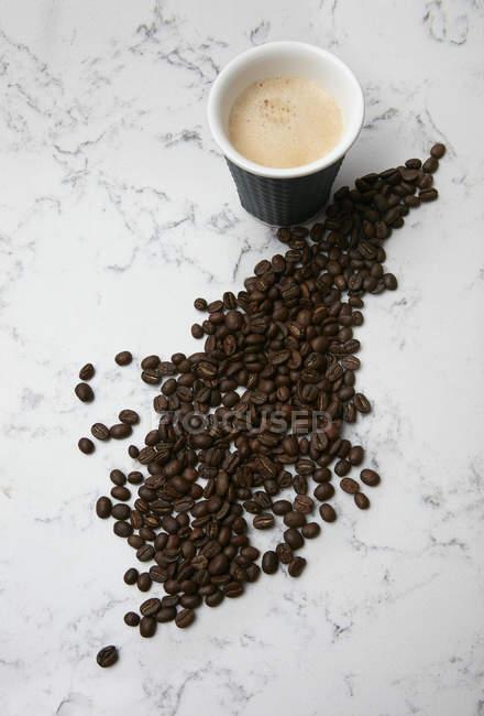 Taza de café y granos de café - foto de stock