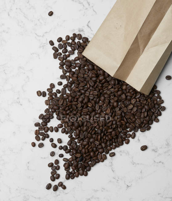 Coffee beans and paper bag — Stock Photo