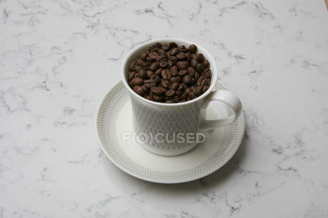 Granos de café en taza de café - foto de stock