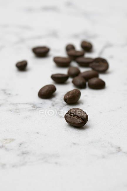 Granos de café sobre mármol - foto de stock