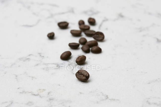 Кава в зернах на мармуру — стокове фото