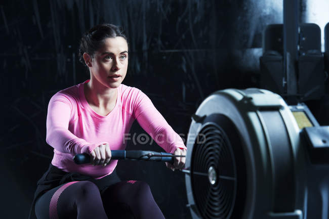 Woman using rowing machine — Stock Photo