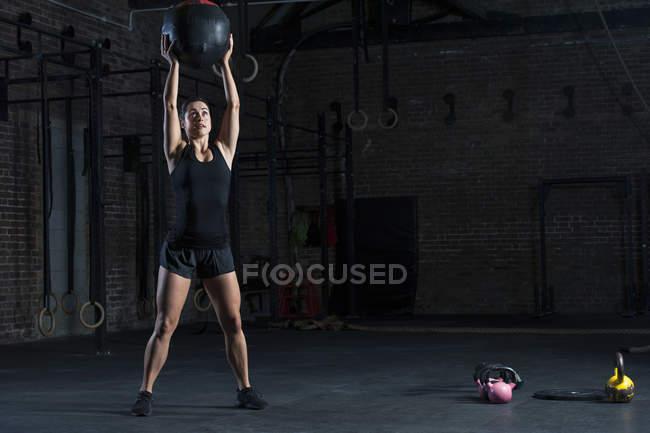 Frau heben Medizinball — Stockfoto