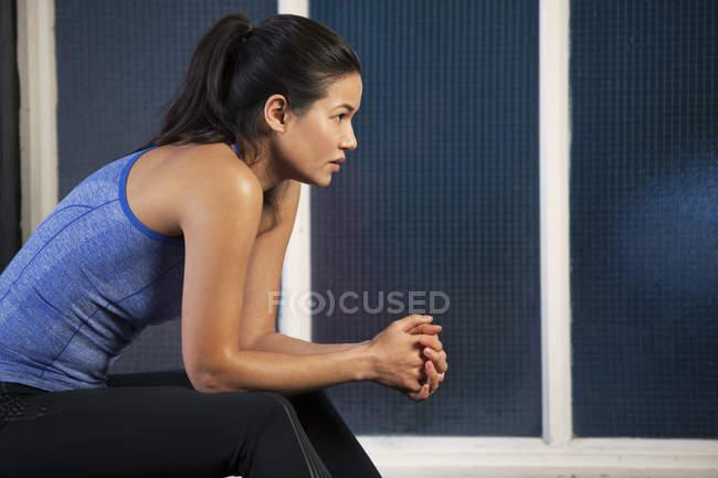 Женщина сидит у окна — стоковое фото
