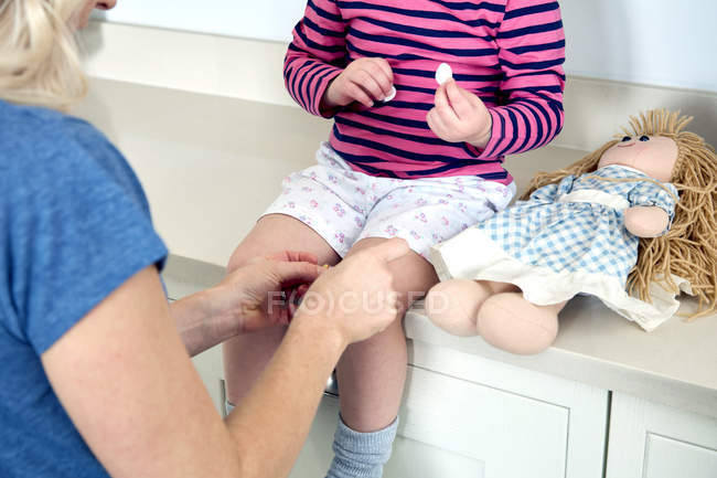 Mother putting bandage on daughters knee — Stock Photo