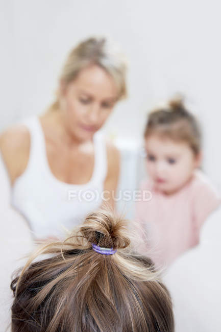 Girl with mother by mirror — Stock Photo