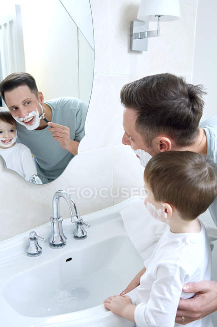 Father shaving face with son — Stock Photo