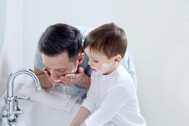 Padre e hijo lavando caras - foto de stock