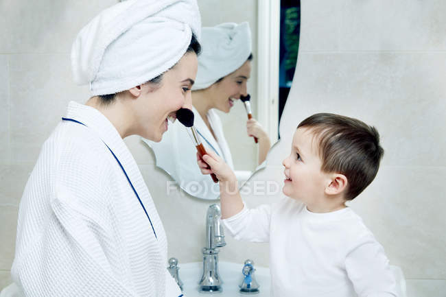 Применение к макияжу мать сын — стоковое фото