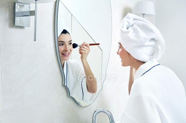 Woman applying make-up with brush — Stock Photo