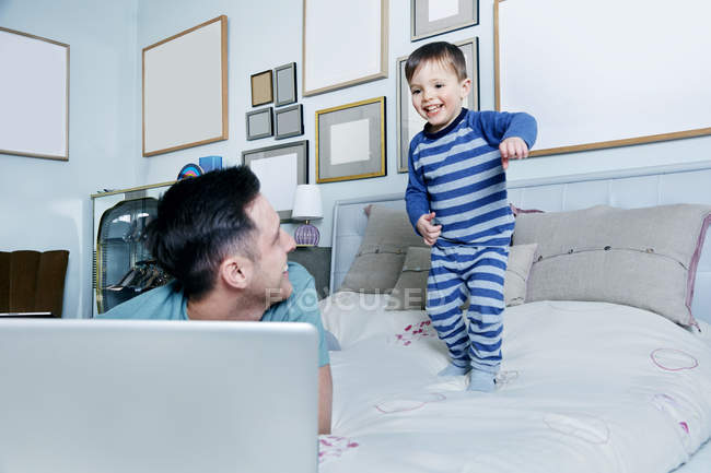 Father and son on bed with laptop — Stock Photo
