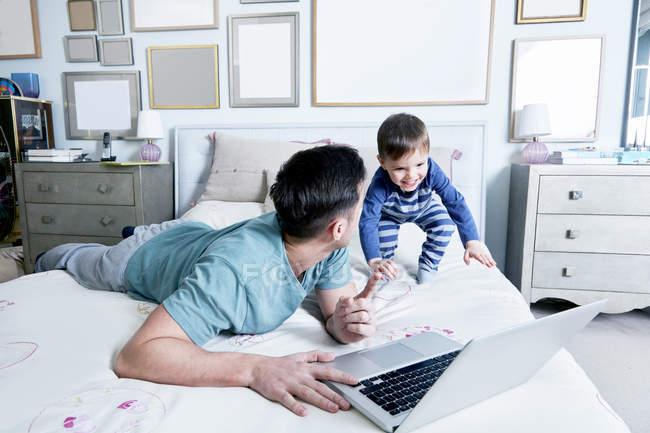 Vater und Sohn auf dem Bett mit laptop — Stockfoto
