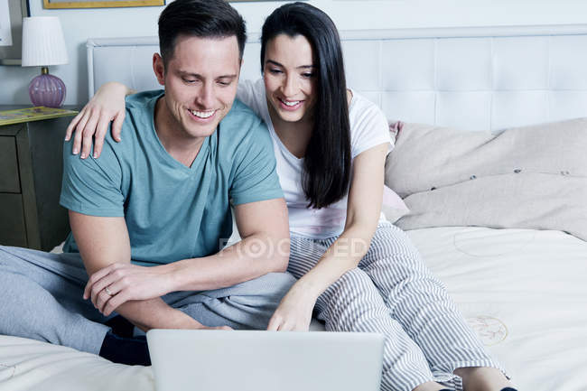 Couple sitting on bed and using laptop — Stock Photo