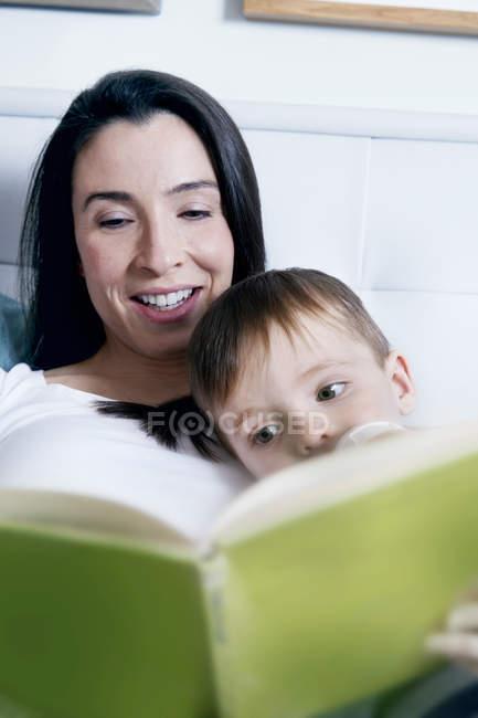 Книга чтение матери к сыну — стоковое фото