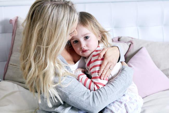 Мать обнимает дочь в постели — стоковое фото