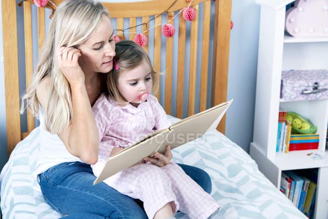 Мати читання книги, щоб дочка — стокове фото
