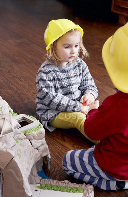 Брат и сестра, носить желтые шлемы — стоковое фото