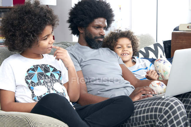 Father and children using laptop on sofa — Stock Photo