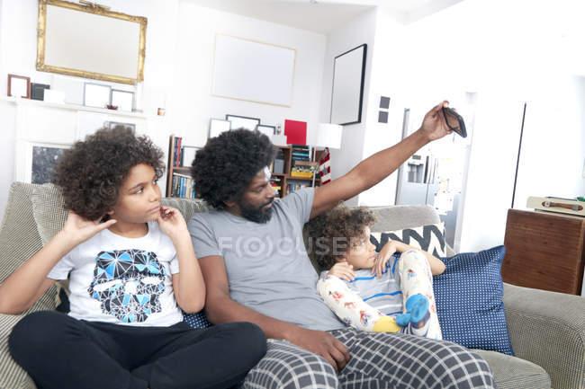 Отец с детьми делает селфи — стоковое фото