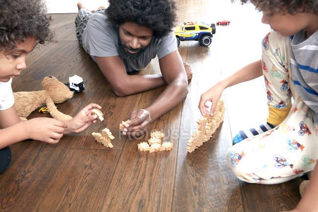 Pai e filhos brincando com blocos — Fotografia de Stock