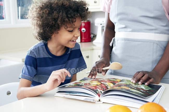 Отец и сын, глядя на книгу рецептов — стоковое фото