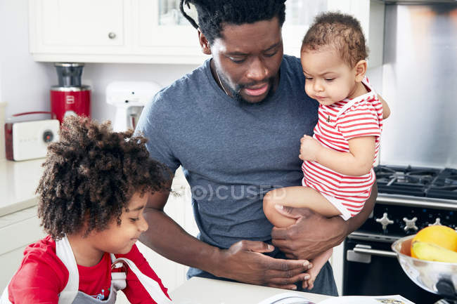 Father with baby on hands looking at recipe book — Stock Photo