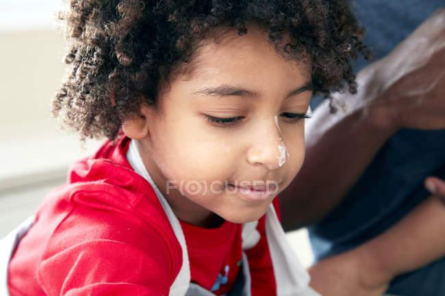 Мальчик с мукой на носу — стоковое фото