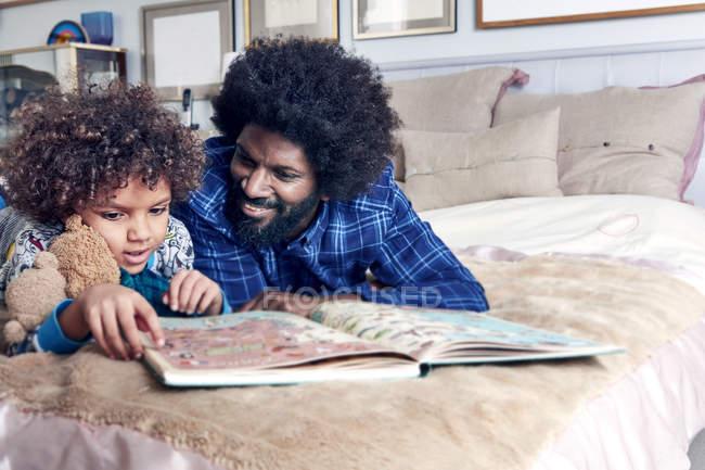 Чтение книги отец сыну на кровати — стоковое фото