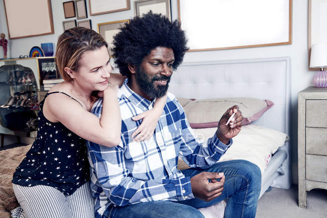 Человек сидит в руке с тест на беременность — стоковое фото