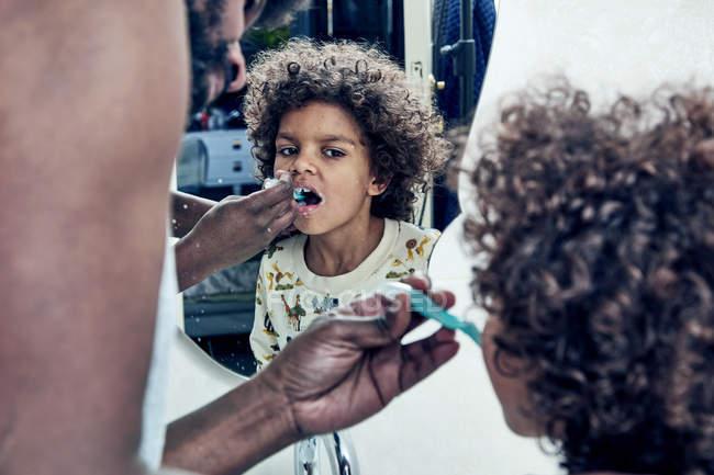 Отец, помогая сын чистить зубы — стоковое фото