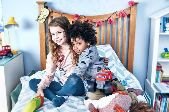 Boy hugging girl on bed — Stock Photo