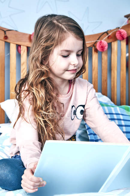 Чтение книги девушка на кровати — стоковое фото
