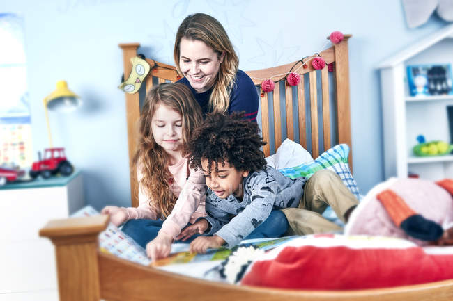 Mother and children reading book on bed — Stock Photo