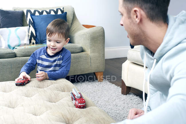 Père et fils jouant avec des voitures jouets — Photo de stock