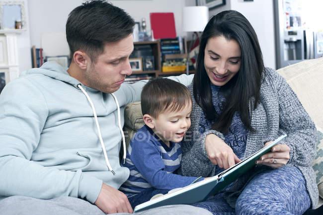 Родители читают книгу с сыном — стоковое фото