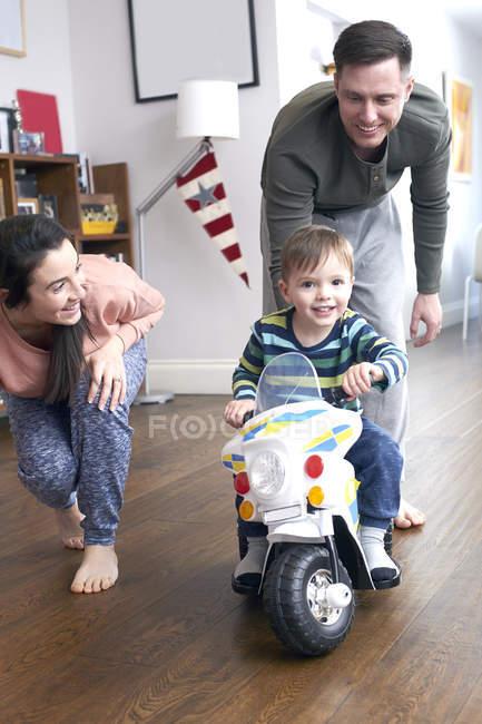 Хлопчик на мотоциклі мініатюрний з батьками — стокове фото