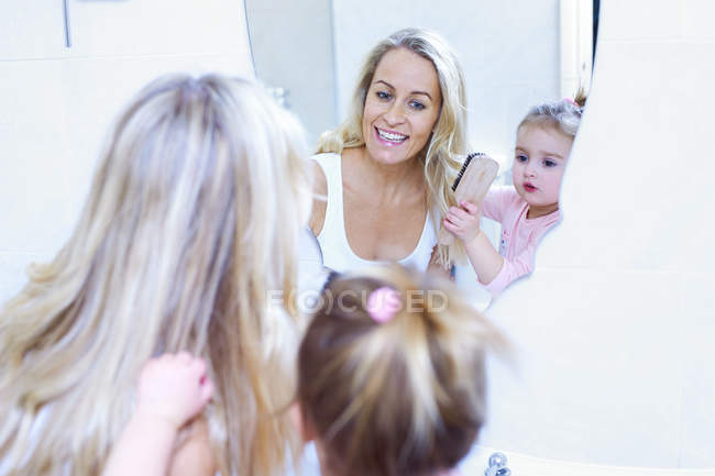 Mother and daughter brushing hair — Stock Photo