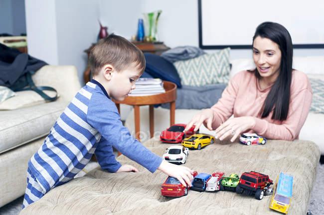 Mãe e filho jogando carros de brinquedo — Fotografia de Stock