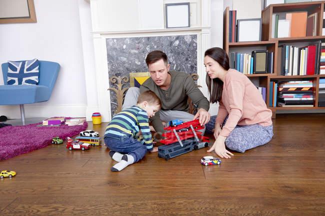 Батьки і син, граючи з іграшками — стокове фото