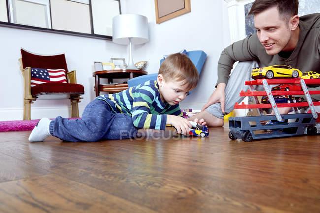Pai e filho brincando com carros de brinquedo — Fotografia de Stock