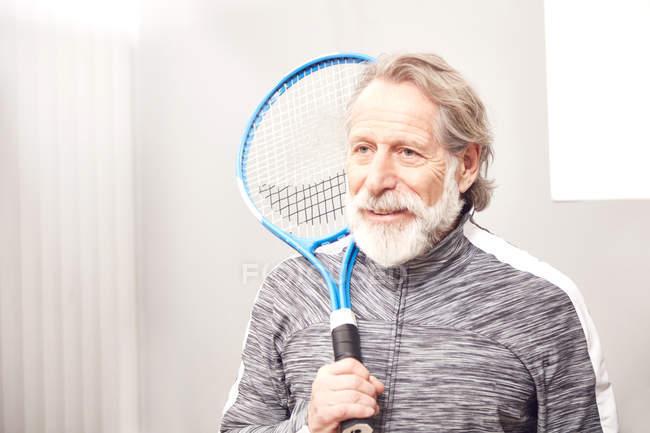 Senior homme debout avec une raquette de tennis — Photo de stock