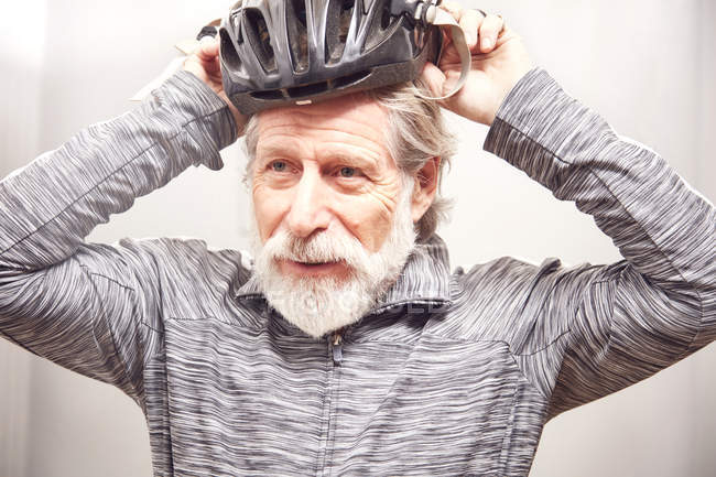 Senior man putting on bicycle helmet — Stock Photo