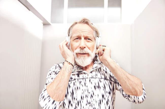 Senior homme, écouter de la musique sur le casque — Photo de stock