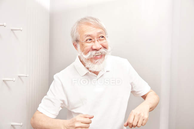 Senior homme en t-shirt blanc souriant — Photo de stock