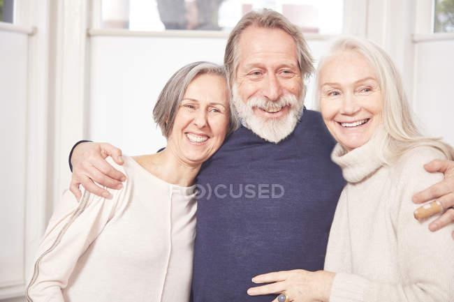 Старший мужчина обнимает подруг — стоковое фото