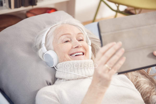 Haute femme à l'aide de tablette numérique — Photo de stock