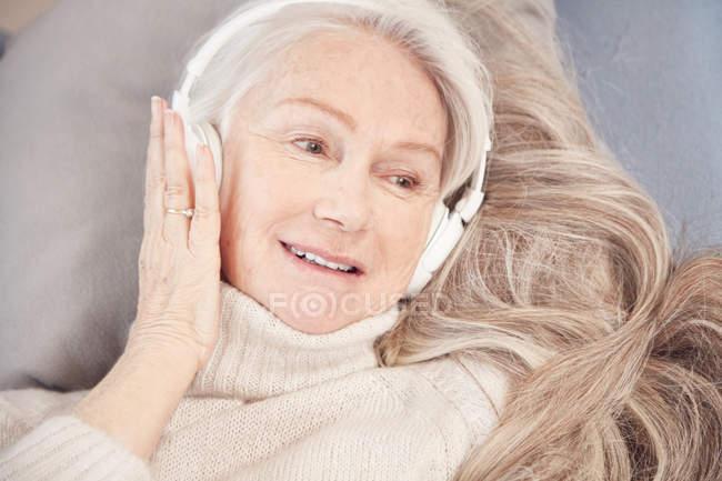 Старшая женщина слушает музыку в наушниках — стоковое фото